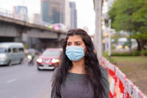 Jeune femme indienne avec masque pensant dans les rues de la ville à l'extérieur