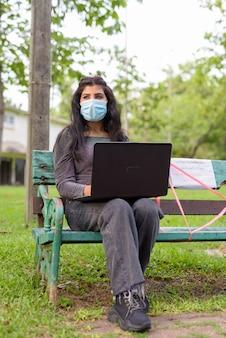 Jeune femme indienne avec masque pensant et utilisant un ordinateur portable alors qu'il était assis avec distance sur banc de parc