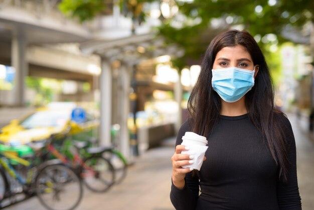 Jeune femme indienne avec masque en train de prendre un café sur le pouce comme la nouvelle norme pendant le covid-19 dans la ville