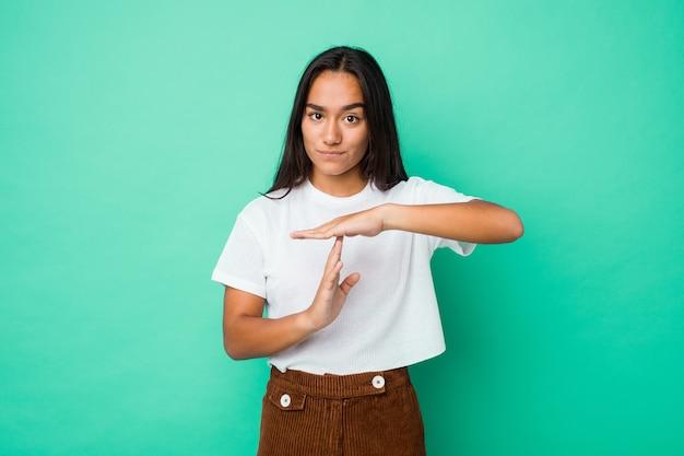 Jeune femme indienne métisse isolée montrant un geste de timeout.