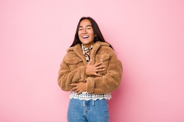 Jeune femme indienne métisse portant un manteau court en peau de mouton, joyeusement et s'amuse à garder les mains sur le ventre.