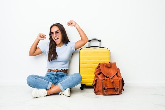 Jeune femme indienne métisse prête à partir en voyage pour célébrer une journée spéciale, saute et lève les bras avec énergie.