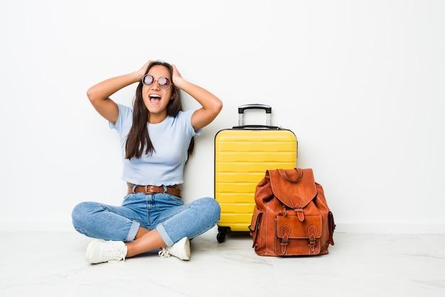 Jeune femme indienne métisse prête à partir voyager, rit joyeusement en gardant les mains sur la tête. notion de bonheur.