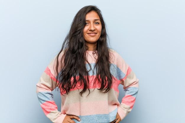 Jeune femme indienne de mode confiant en gardant les mains sur ses hanches