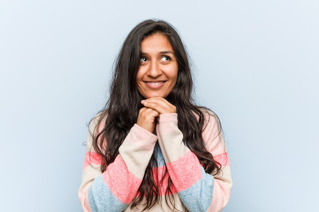 Jeune femme indienne de mode garde les mains sous le menton, cherche heureusement de côté.