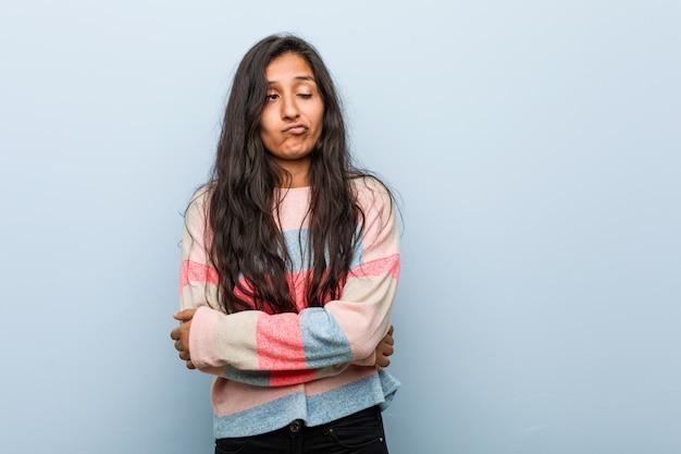 Jeune femme indienne de mode malheureuse regardant à huis clos avec une expression sarcastique