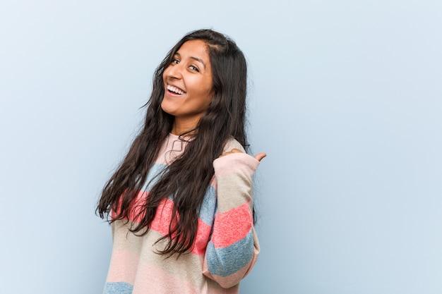 Jeune femme indienne de mode pointe avec le pouce loin, rire et insouciant