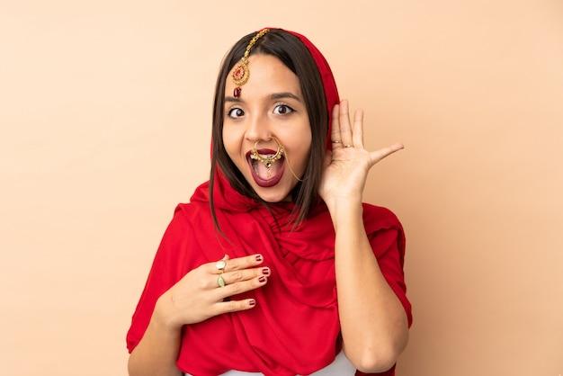 Jeune femme indienne sur mur beige écouter quelque chose en mettant la main sur l'oreille