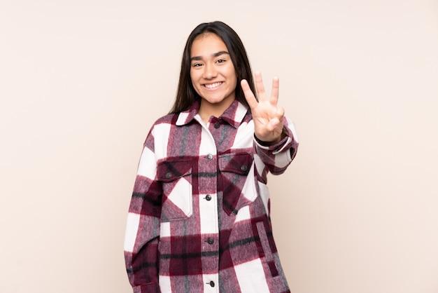 Jeune femme indienne sur mur beige heureux et en comptant trois avec les doigts