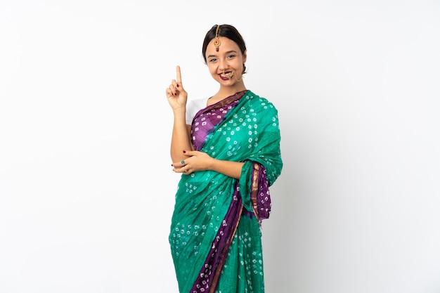 Jeune femme indienne sur mur blanc montrant et levant un doigt
