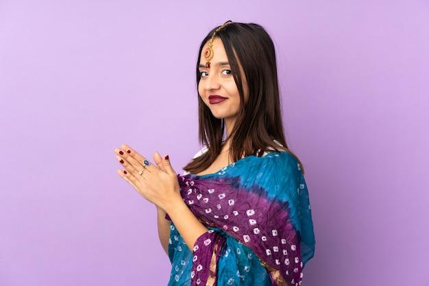 Jeune femme indienne sur mur violet complotant quelque chose