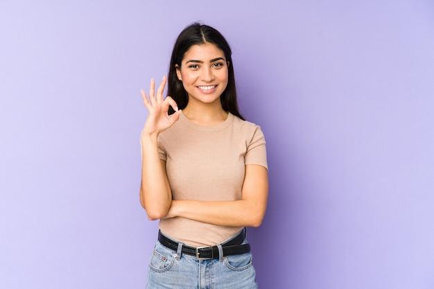 Jeune femme indienne sur le mur violet fait un clin d'œil et tient un geste correct avec la main.