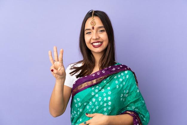 Jeune femme indienne sur mur violet heureux et en comptant trois avec les doigts