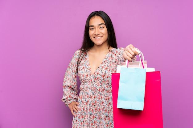 Jeune femme indienne sur un mur violet tenant des sacs à provisions et les donnant à quelqu'un