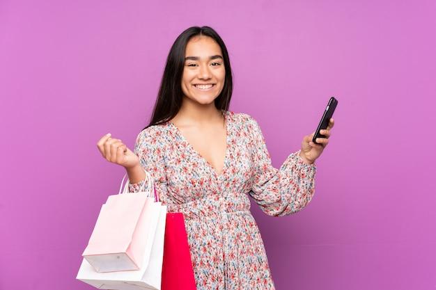 Jeune femme indienne sur un mur violet tenant des sacs à provisions et écrivant un message avec son téléphone portable à un ami