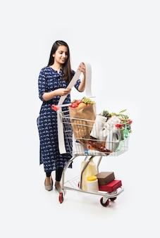 Jeune femme indienne avec panier ou chariot plein d'épicerie, de légumes et de fruits. photo pleine longueur isolée sur mur blanc