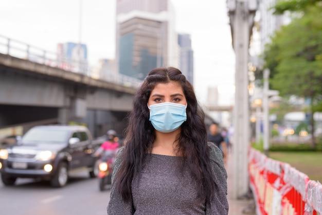 Jeune femme indienne portant un masque pour se protéger contre l'épidémie de coronavirus et la pollution dans les rues de la ville à l'extérieur