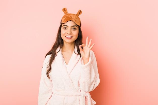 Jeune femme indienne portant un pyjama et un masque de sommeil isolé gai et confiant montrant le geste ok.