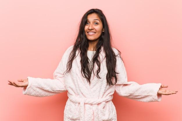 Jeune femme indienne portant un pyjama montrant une expression bienvenue.