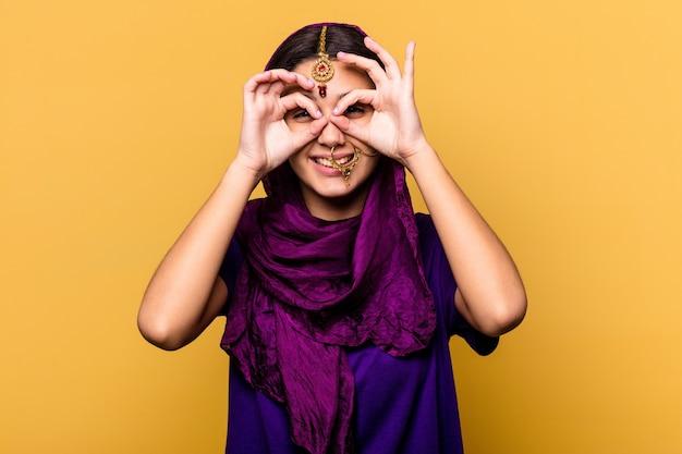 Jeune femme indienne portant un vêtement sari traditionnel isolé sur un mur jaune montrant un signe correct sur les yeux
