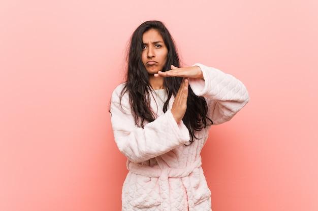 Jeune femme indienne porte un pyjama montrant un geste de délai d'attente.