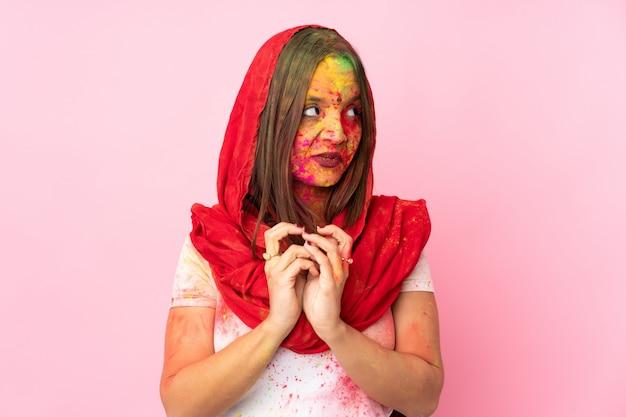 Jeune femme indienne avec des poudres de holi colorées sur son visage isolé sur un mur rose complotant quelque chose
