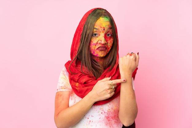 Jeune femme indienne avec des poudres de holi colorées sur son visage isolé sur un mur rose faisant le geste d'être en retard