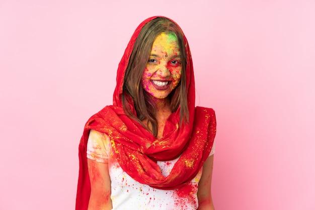 Jeune femme indienne avec des poudres de holi colorées sur son visage isolé sur un mur rose en riant