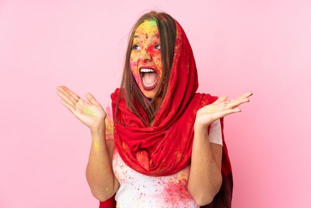 Jeune femme indienne avec des poudres de holi colorées sur son visage isolé sur mur rose