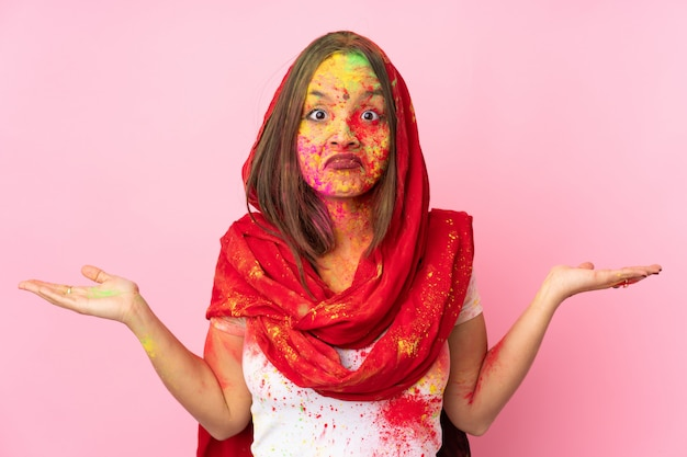 Jeune femme indienne avec des poudres de holi colorées sur son visage sur le mur rose ayant des doutes tout en levant les mains