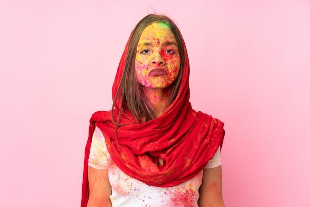 Jeune femme indienne avec des poudres de holi colorées sur son visage sur un mur rose avec une expression triste