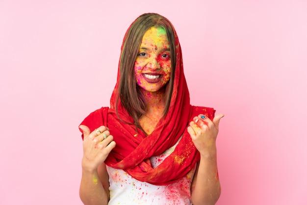 Jeune femme indienne avec des poudres de holi colorées sur son visage sur un mur rose avec le geste du pouce en l'air et souriant