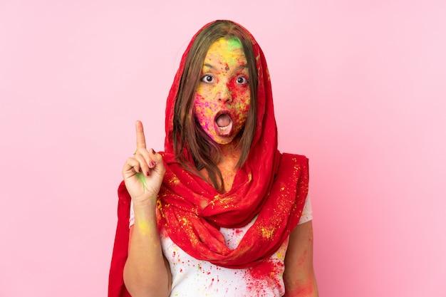 Jeune femme indienne avec des poudres de holi colorées sur son visage sur le mur rose en pensant à une idée pointant le doigt vers le haut