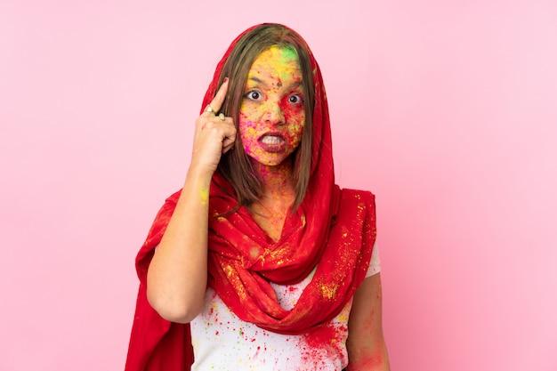 Jeune femme indienne avec des poudres de holi colorées sur son visage sur le mur rose en pensant à une idée