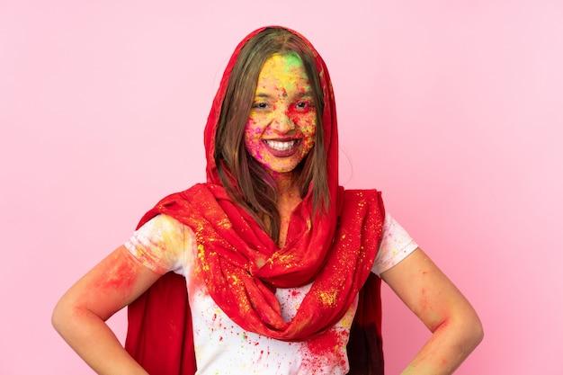 Jeune femme indienne avec des poudres de holi colorées sur son visage sur un mur rose posant avec les bras à la hanche et souriant