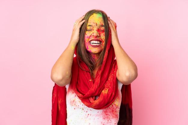 Jeune femme indienne avec des poudres de holi colorées sur son visage sur le mur rose en riant