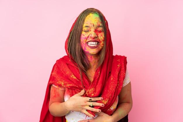 Jeune femme indienne avec des poudres de holi colorées sur son visage sur un mur rose souriant beaucoup