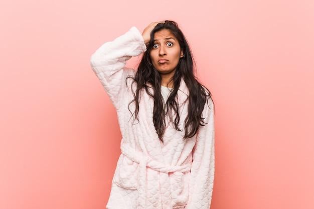 Jeune femme indienne en pyjama étant sous le choc, il s'est souvenu d'une réunion importante.