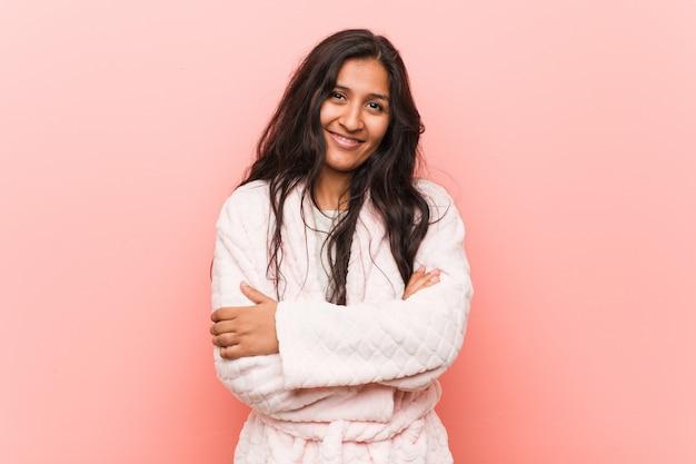Jeune femme indienne en pyjama qui se sent confiant, croisant les bras avec détermination