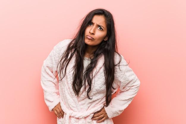 Jeune femme indienne en pyjama réprimande quelqu'un très en colère.