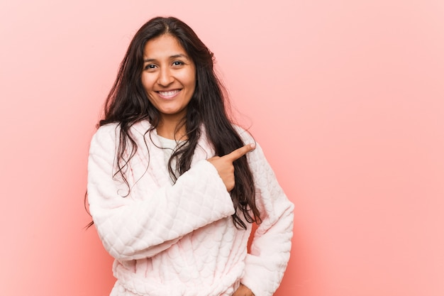 Jeune femme indienne en pyjama souriant et pointant à côté, montrant quelque chose dans un espace vide.