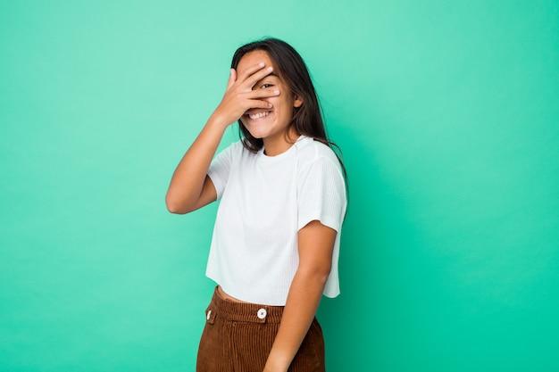 Jeune femme indienne de race mixte cligner des yeux à la caméra à travers les doigts, embarrassé couvrant le visage.