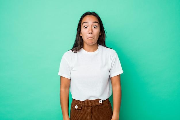 Jeune femme indienne de race mixte isolée hausse les épaules et les yeux ouverts confus.
