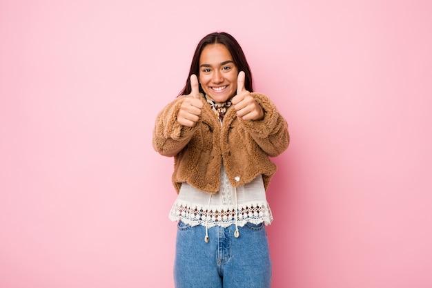 Jeune femme indienne de race mixte portant un manteau court en peau de mouton avec les pouces vers le haut, applaudit à quelque chose, soutient et respecte le concept.