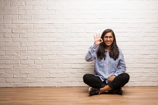Jeune femme indienne s'asseoir contre un mur de briques gai et confiant faisant geste ok