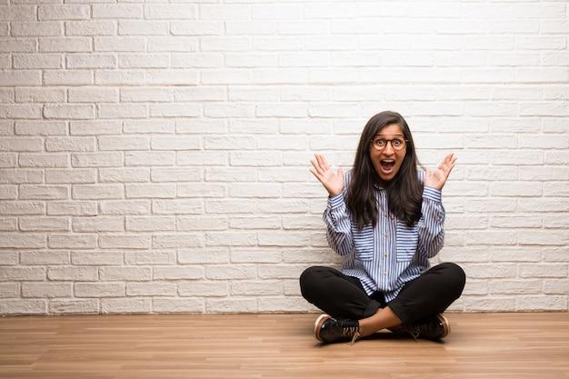 Jeune femme indienne s'asseoir contre un mur de briques hurlant de joie, surprise par une offre ou un pr