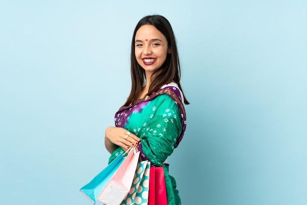Jeune femme indienne avec des sacs à provisions avec bras croisés et impatient