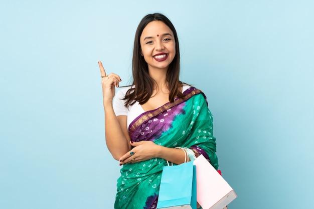 Jeune femme indienne avec des sacs à provisions heureux et pointant vers le haut