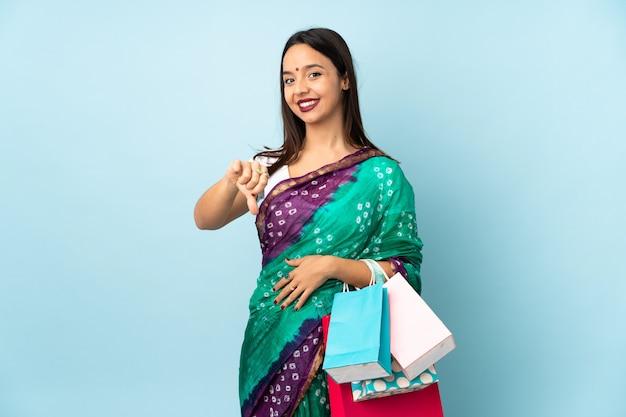 Jeune femme indienne avec des sacs à provisions montrant le pouce vers le bas avec une expression négative
