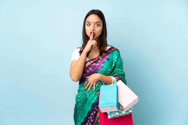 Jeune femme indienne avec des sacs à provisions montrant un signe de silence mettant le doigt dans la bouche